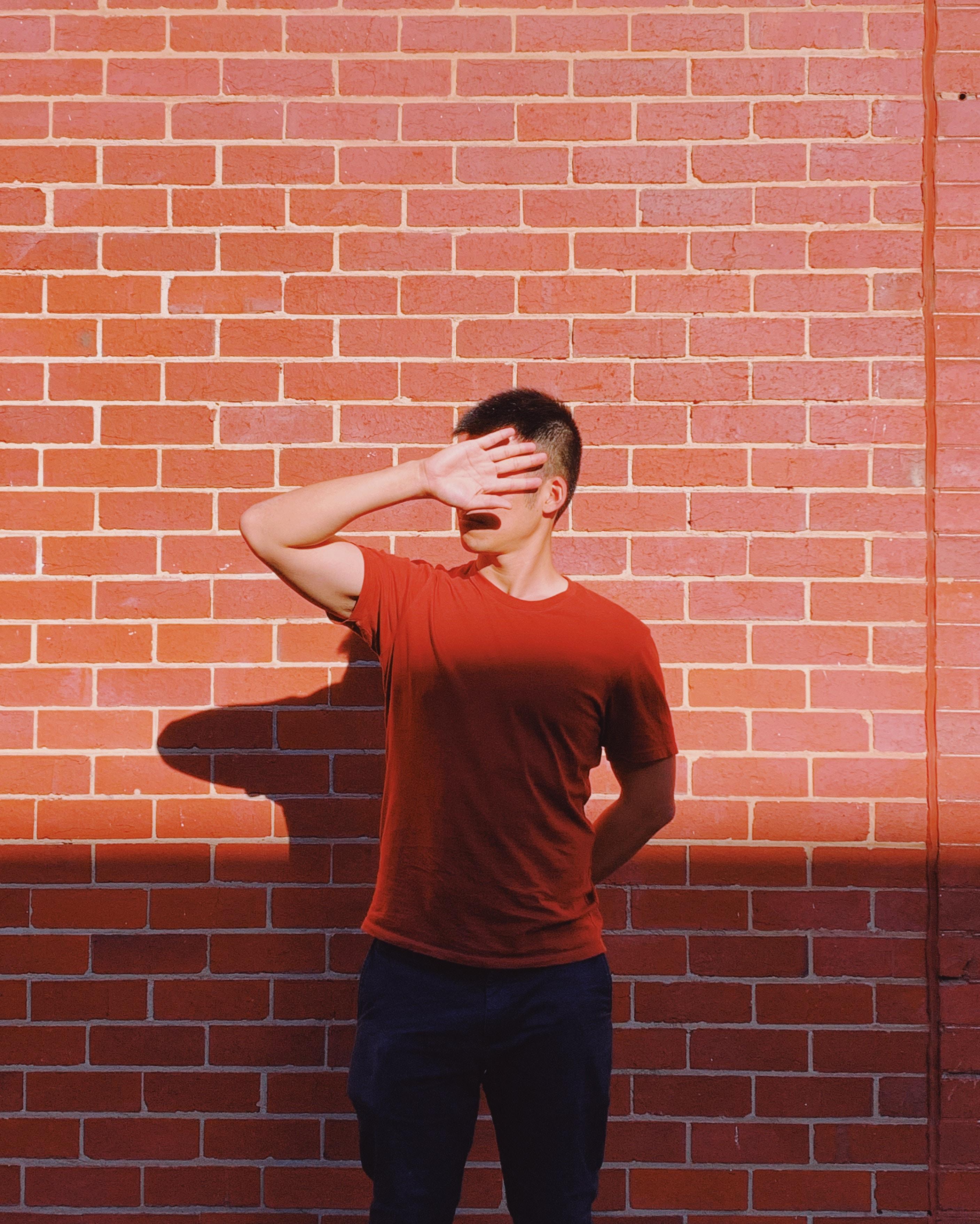 Start up - czym nie jest? Mężczyzna stojący na tle ceglanej ściany, zasłaniający twarz ręką, ponieważ nie chce patrzeć na złe definicje.