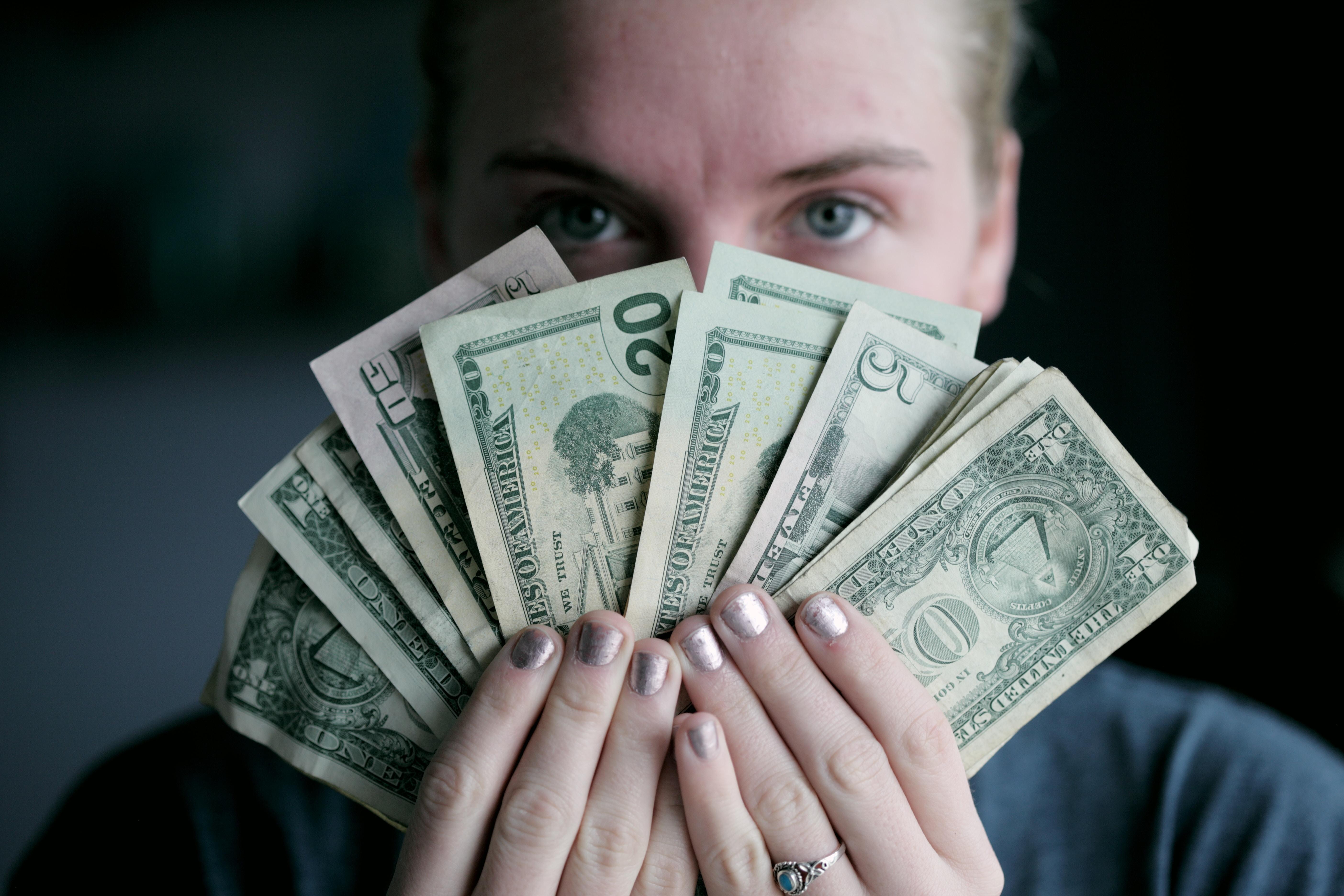 Kobieta trzymająca banknoty amerykańskie, które demonstrują z jaką łatwością zaoszczędziliśmy kupę pieniędzy dla naszego klienta dzięki przygotowaniu analizy projektowej.